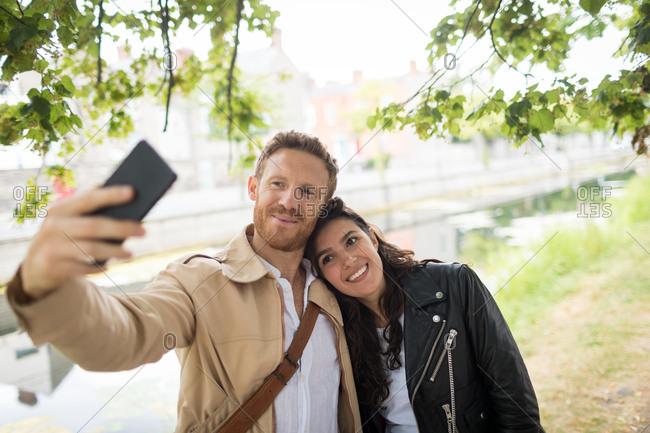 Romantic couple taking selfie near lake side