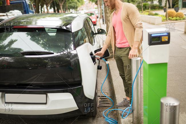 Smart man charging electric car at charging station