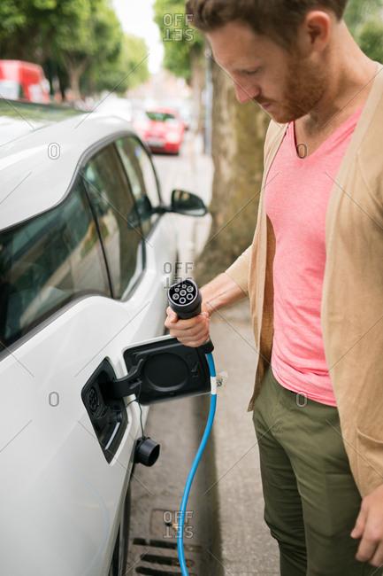 Smart man checking plug of charger at charging station