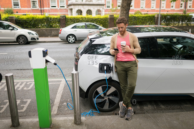 Smart man using mobile phone at charging station