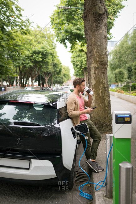 Man having coffee while using mobile phone at charging station