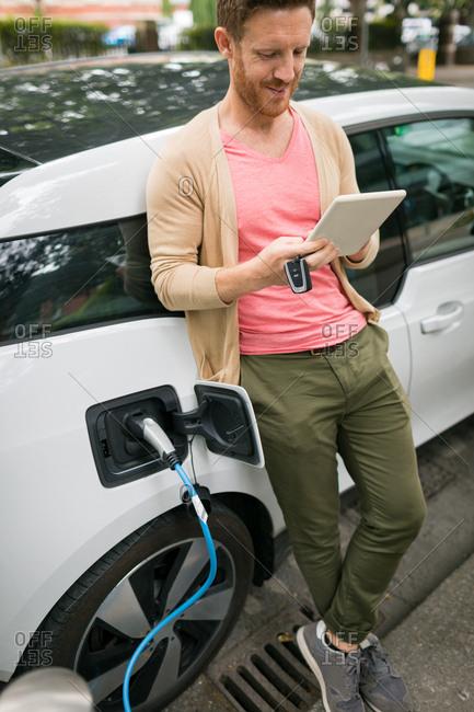 Man using digital tablet while charging electric car at charging station