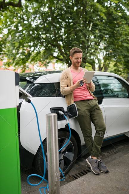 Man using digital tablet while charging electric car at charging station