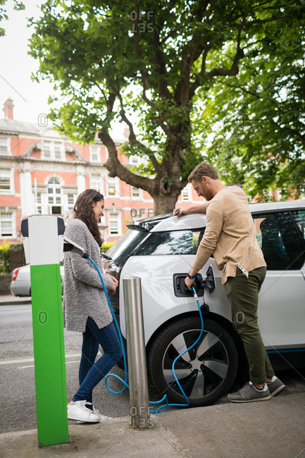 Couple charging electric car at charging station