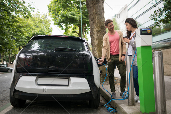 Couple interacting with each other while charging electric car at charging station