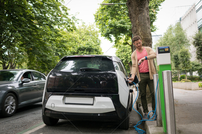 Man checking time on smart watch while charging electric car at charging station