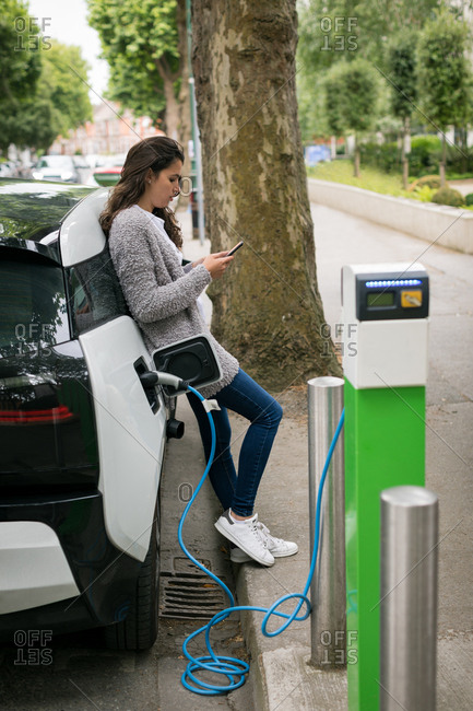 Woman using mobile phone while charging electric car at charging station