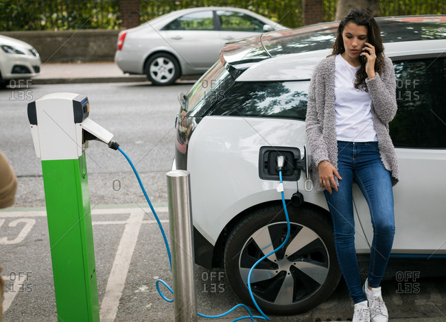 Woman talking on mobile phone while charging electric car at charging station