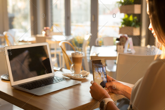 Woman taking photo of coffee cup with mobile phone in cafe