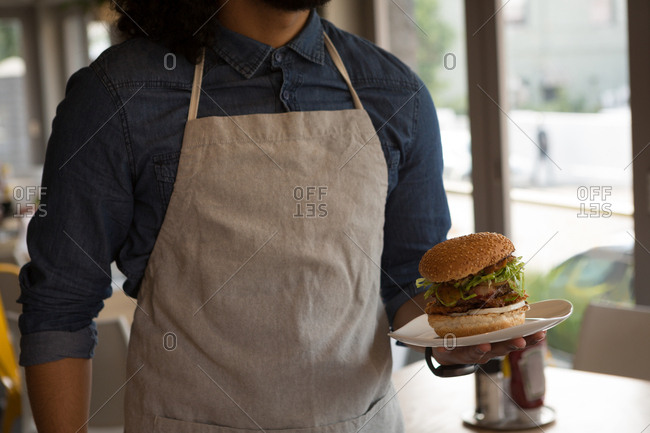 Mid section of waiter holding hamburger in cafe