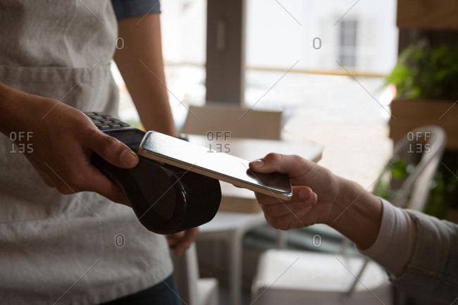 Close-up of woman paying with NFC technology on mobile phone in cafe