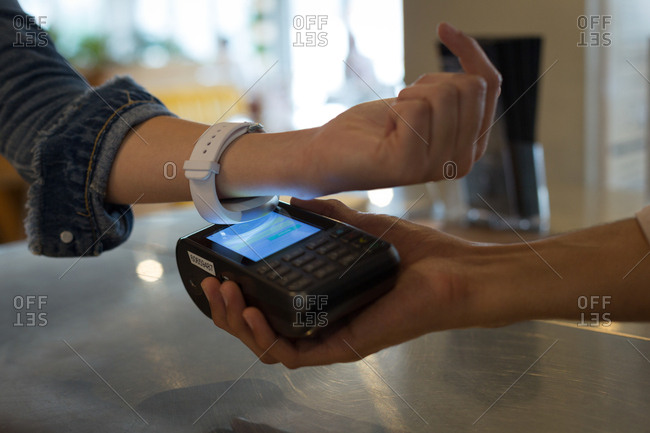 Close-up of woman paying with NFC technology on smartwatch in cafe