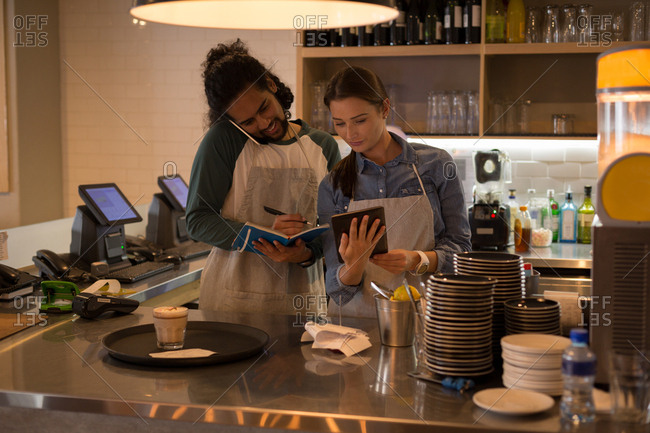 Waiters working at coffee counter in cafe