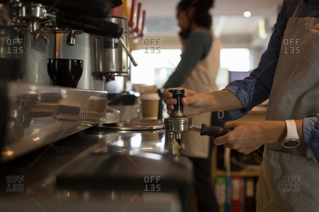 Mid section of waitress preparing coffee at coffee machine in cafe