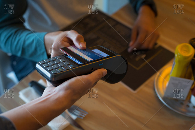 Close-up of man paying with NFC technology on credit card in cafe