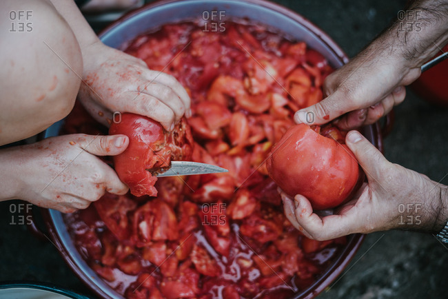 Male and female hands slicing tomatoes