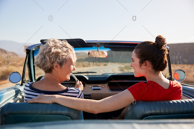 Mum and adult daughter in open top car, back view, close up