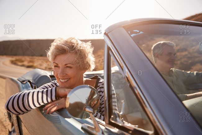 Senior couple driving open top car on desert road, close up