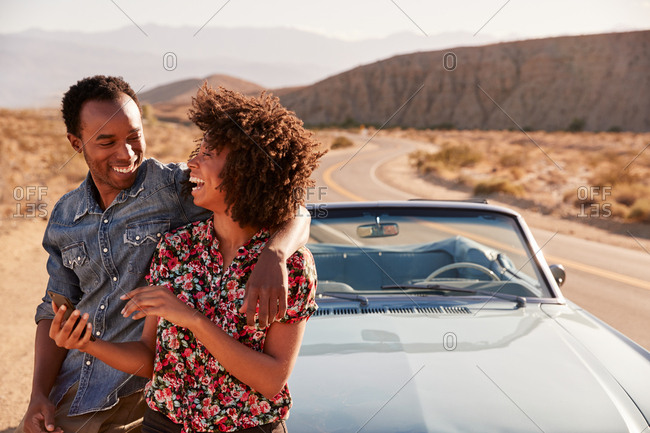 Young black couple checking map on smartphone at roadside