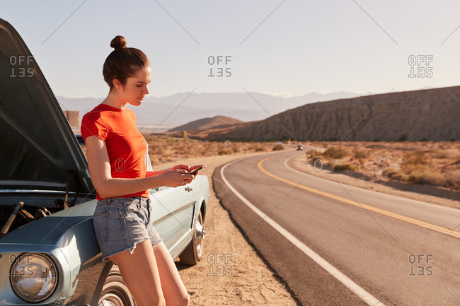 Young white woman leaning on broken down car using her phone