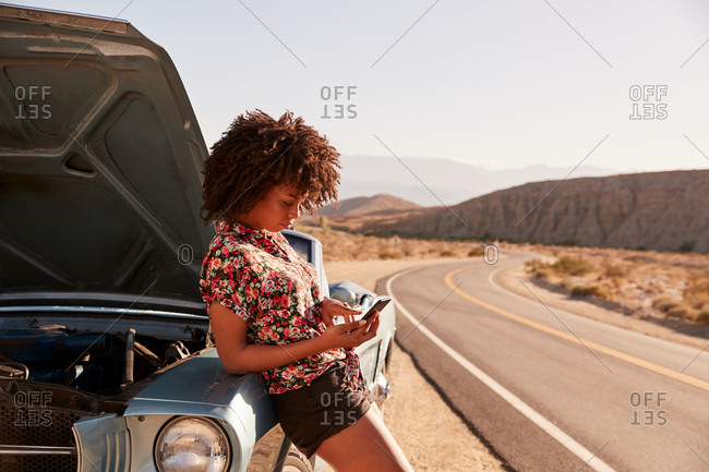 Young black woman leaning on broken down car using her phone
