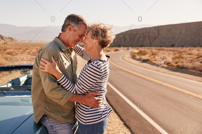 Senior white couple embracing by their car at the roadside