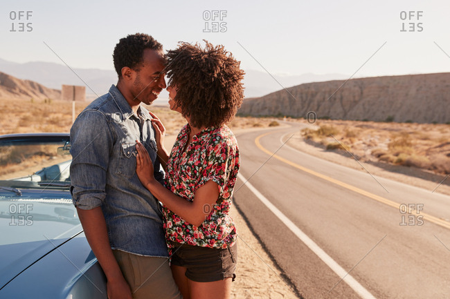 Young black couple embracing by their car at the roadside