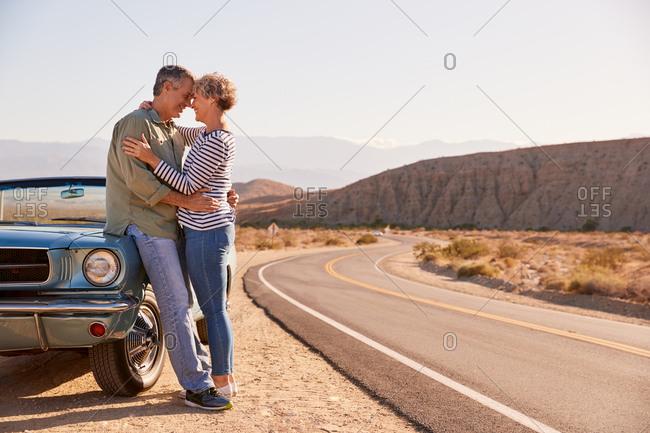 Senior white couple embrace by car at roadside, full length