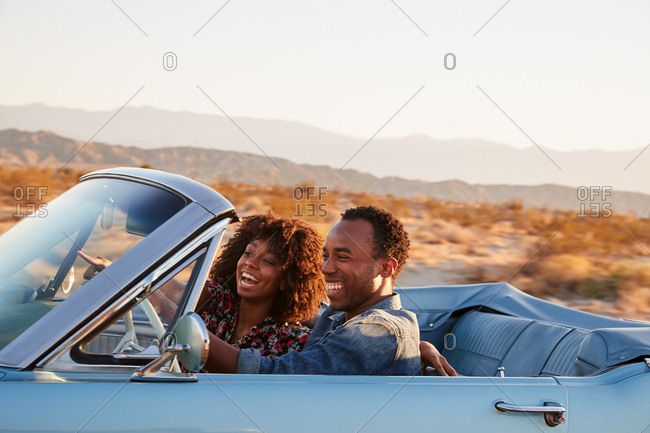 Young black couple driving on a desert highway, close up
