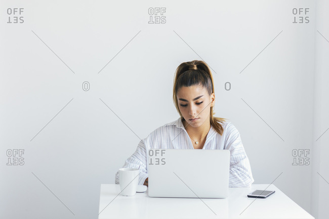 Woman sitting at desk working on laptop computer
