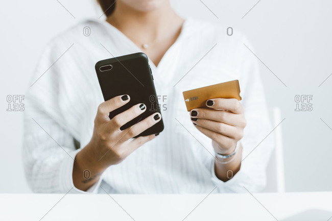 Woman holding contactless credit card next to phone