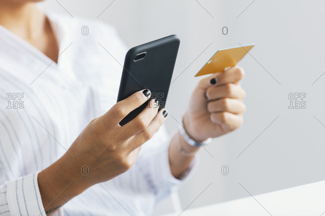 Close-up of woman holding smartphone and contactless credit card