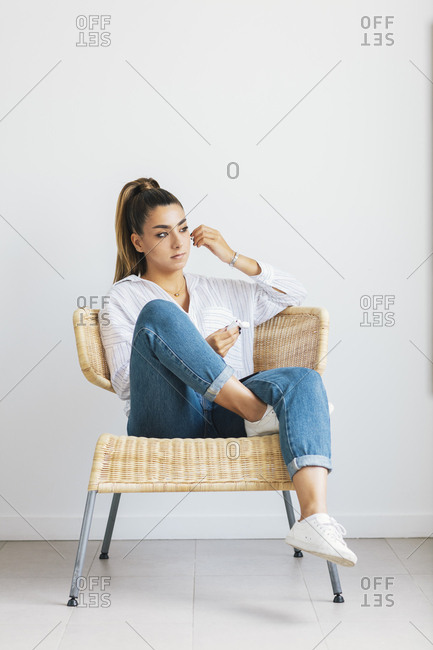 Young Woman Relaxing In Chair And Putting On Wireless Earbuds Stock Photo Offset