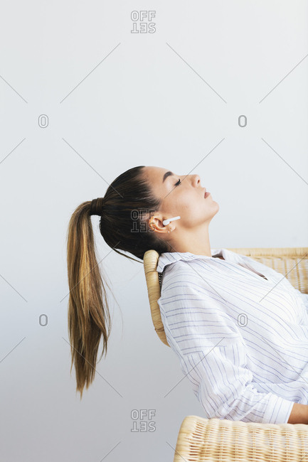 Young woman using wireless earbuds reclining in chair with eyes closed