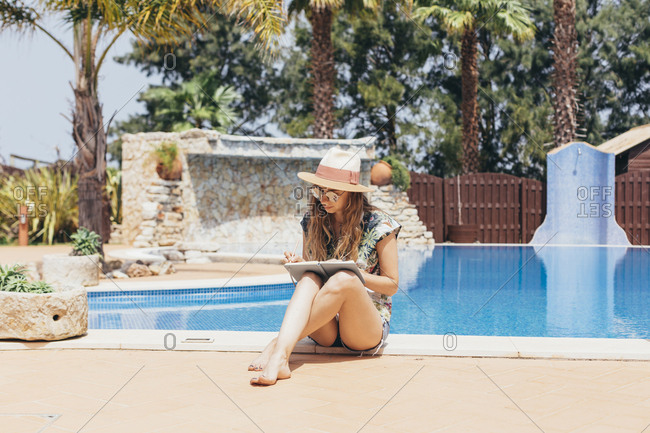 Young woman sitting poolside writing in journal