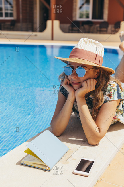 Young woman lying poolside beside her journal