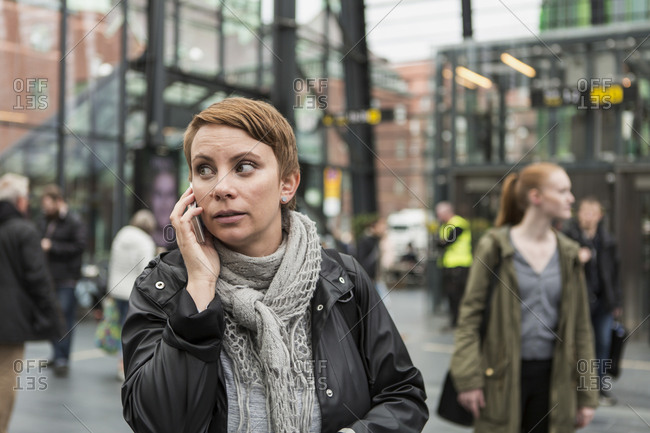 Mid adult woman talking on mobile phone with friend in background at station