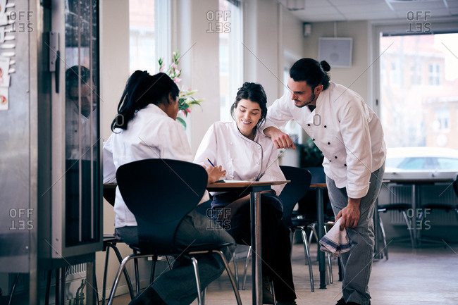 Multi-ethnic male and female chefs discussing menu in restaurant