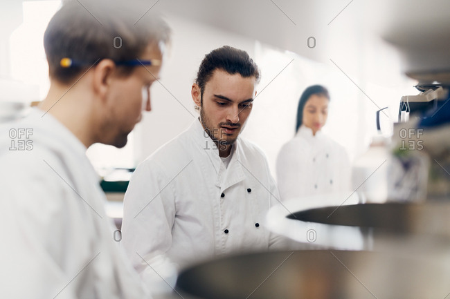 Young male chef with colleague cooking food in commercial kitchen
