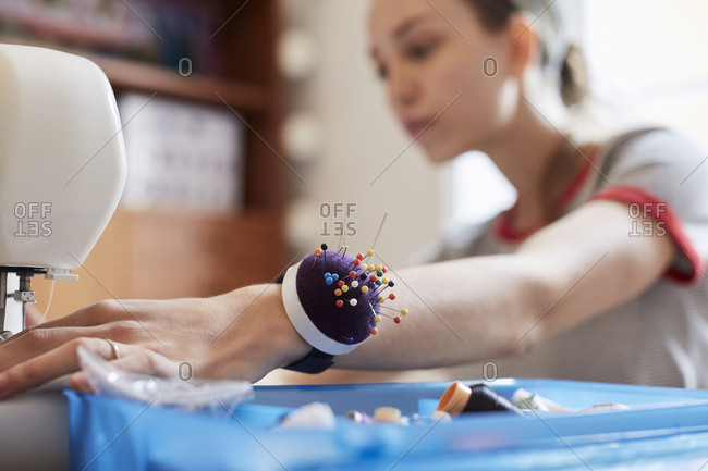 Close up of female tailor wearing pin cushion on wrist while using sewing machine at table
