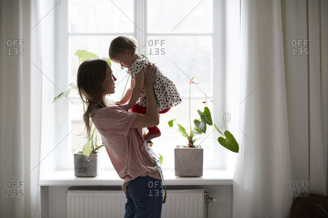 Side view of fashion designer carrying daughter while standing by window at home