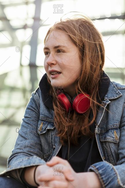 Teenage girl in denim jacket with red headphones looking away