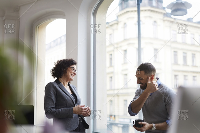 Smiling business colleagues communicating at office