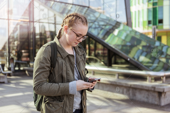 Teenage girl using mobile phone while standing against building in city
