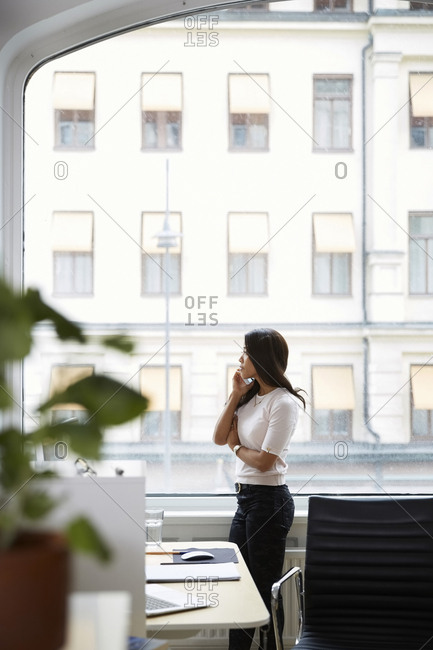 Side view of mature woman talking on mobile phone while looking through window at office