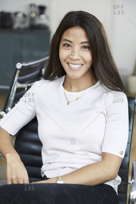 Portrait of smiling businesswoman sitting on chair at office