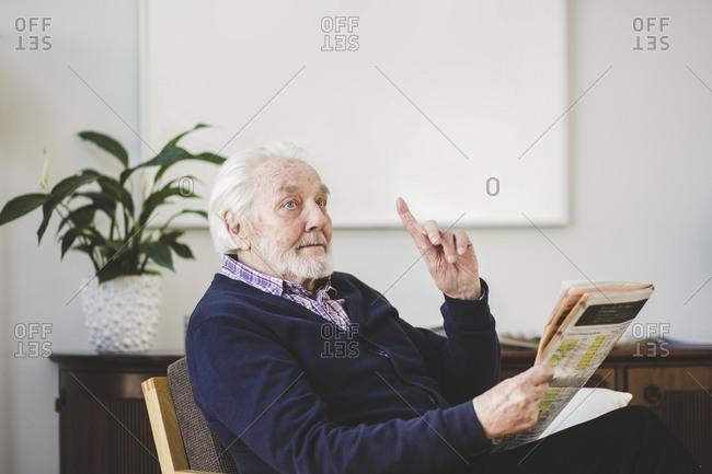 Senior man pointing while holding newspaper in nursing home