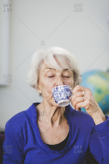 Senior woman with eyes closed having drink in nursing home
