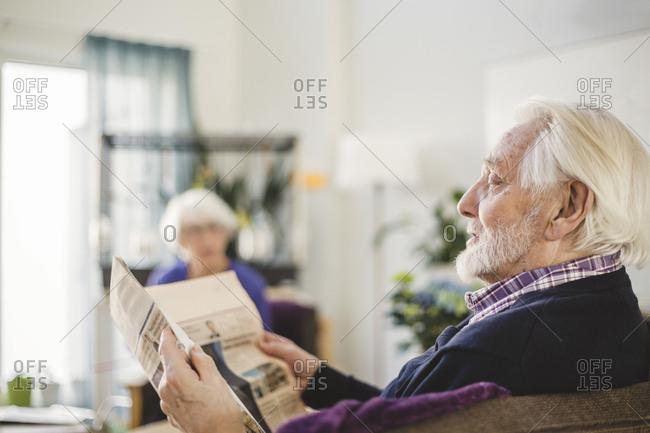 Senior man reading newspaper while sitting on sofa in nursing home