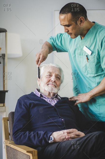 Mature male caregiver combing hair of senior man sitting on chair in nursing home